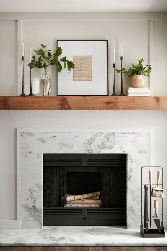 Floating wood mantel above marble fireplace with candlesticks and plants