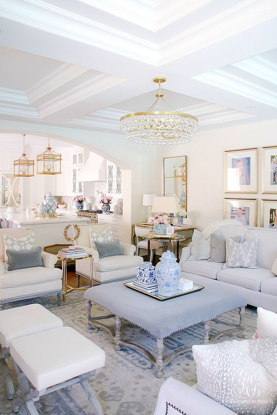 Elegant formal living room with white walls and furniture and pops of blue and pink.