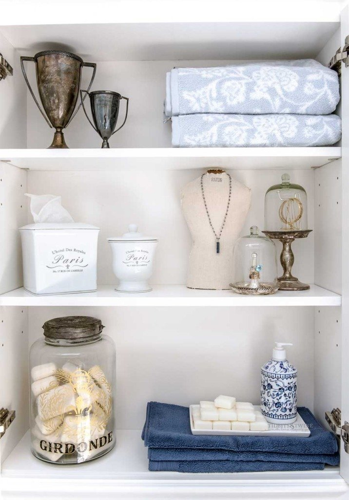 white bathroom shelves styled with vintage trophy cups and jewelry cloches