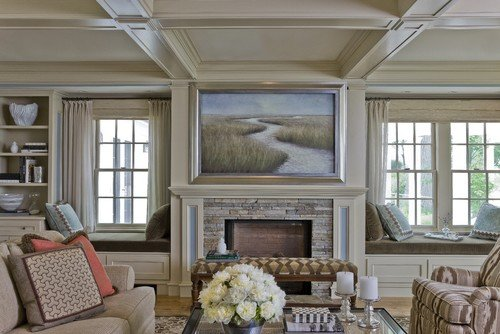 tv above fireplace that is covered by artwork