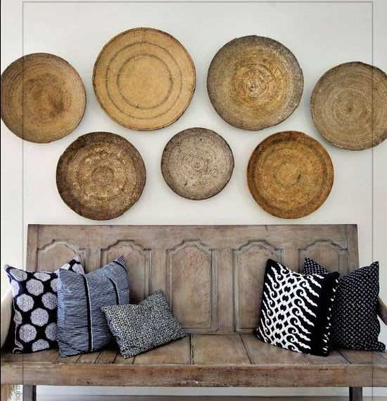 Collection of round baskets hanging above a wooden bench