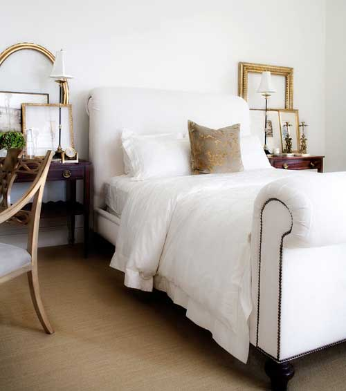 Gold frames leaning on nightstands in a bedroom with white upholstered bed