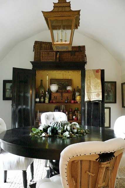 Black armoire used as a bar with round table and rustic lantern hanging above