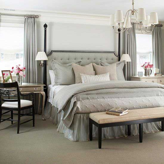 Black four poster bed with gray tufted headboard gray walls and gray curtains