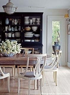 Dining room with black buffet filled with white dishes and oval dining table