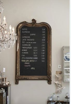Black chalkboard inside an antique gold frame in a kitchen