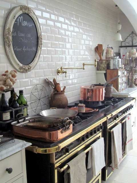 Black stove with gold accents in a kitchen with white subway tile and copper pots