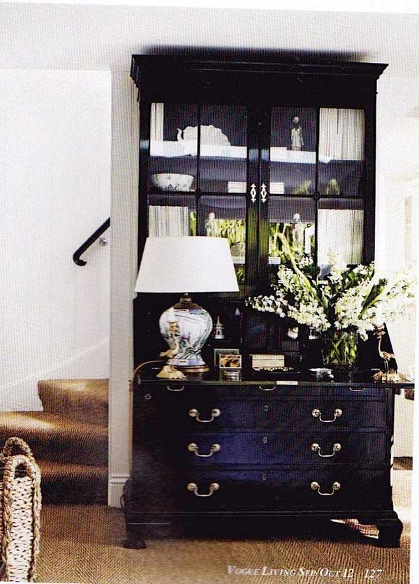 Large black secretary desk with lamp and white flowers on top and textured rug