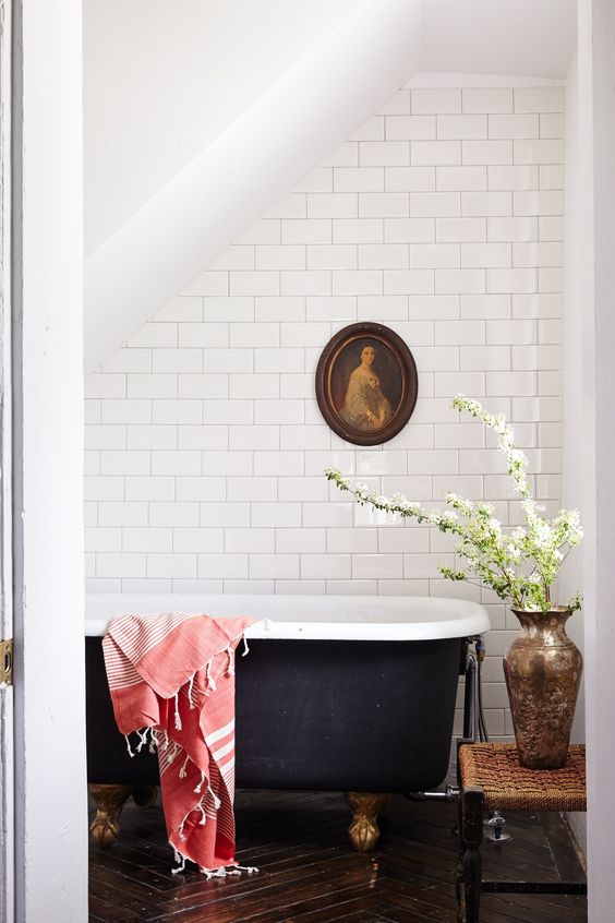 bathroom with black clawfoot tub and white tile surround