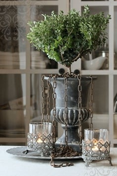 Black urn with a boxwood topiary planted in it and chains hanging down on dining table