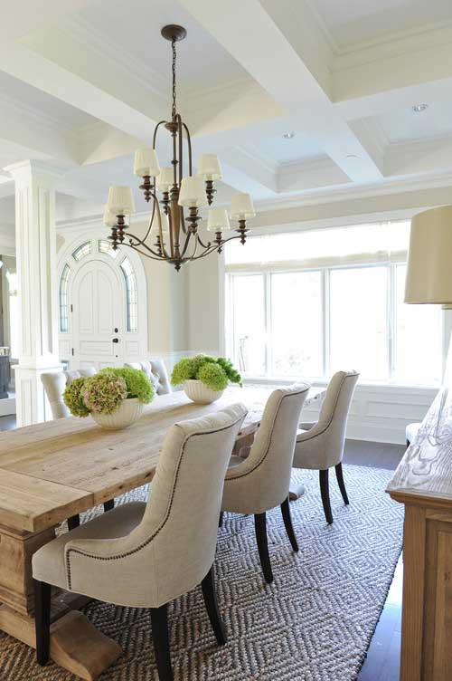 Dining room with rustic table and contemporary beige dining chairs and hydrangea centerpiece