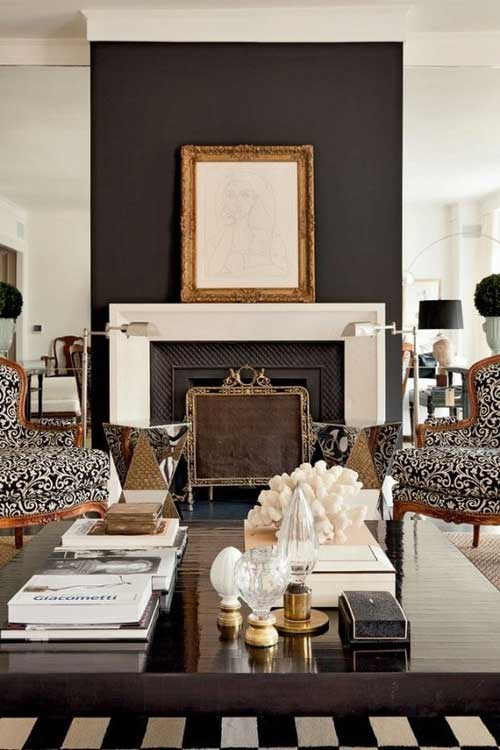 Modern room with black painted wall behind the fireplace and gold framed art on mantel
