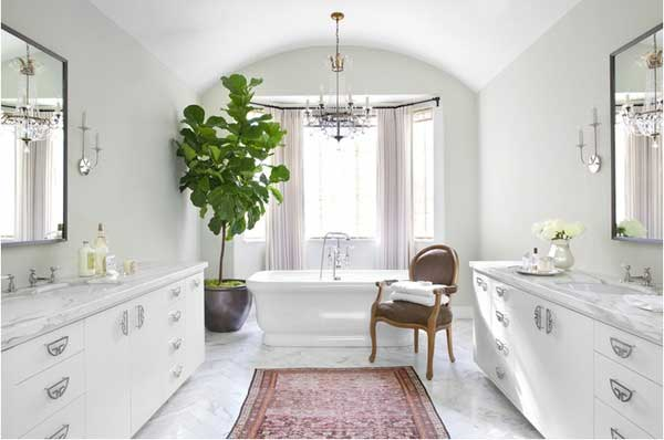 White marble bathroom with window behind freestanding tub and large fiddle leaf fig in corner