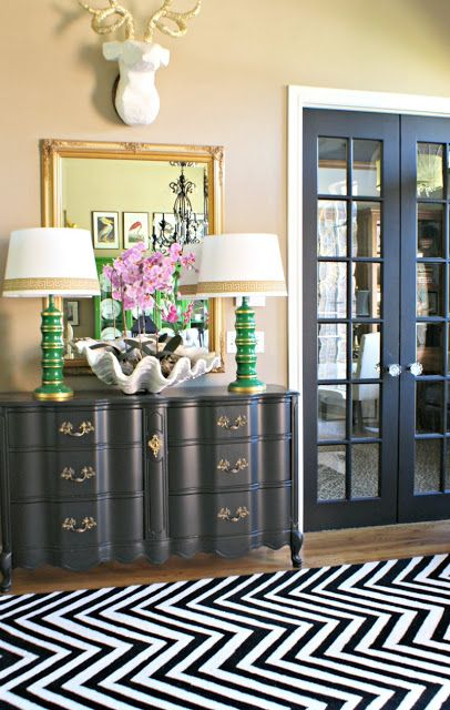 Entryway with black dresser with green lamps on top and large clamshell with purple orchid inside