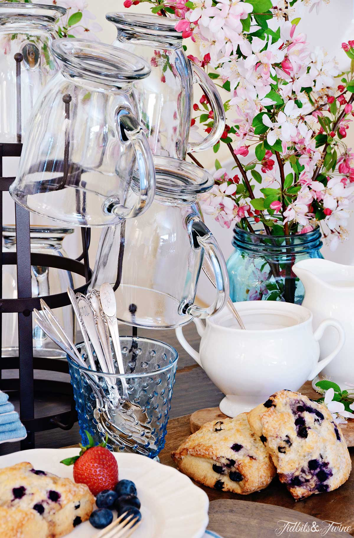 Closeup of bottle drying rack holding clear coffee mugs next to vase of cherry blossoms and plate of scones