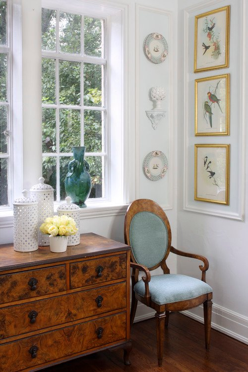 Corner of room with a small chest of drawers and a blue French chair and gold framed bird prints on the wall