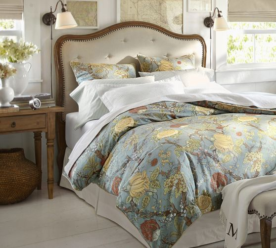 Bedroom with tufted headboard with floral bedding and two plug-in sconces on sides of bed