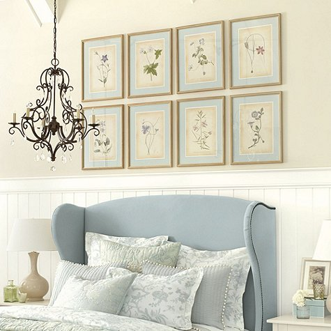 Bedroom with blue wingback bed and eight flower prints hanging on the wall above