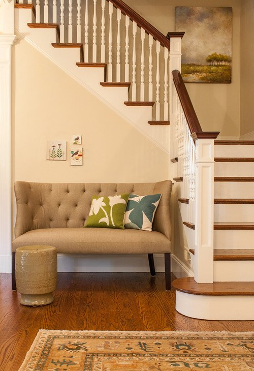 Foyer with small beige tufted settee at the bottom of the stairs