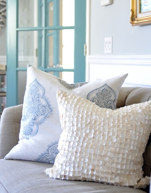 Closeup of two pillows on a beige sofa one pillow is blue and white and one is a white seashell pillow