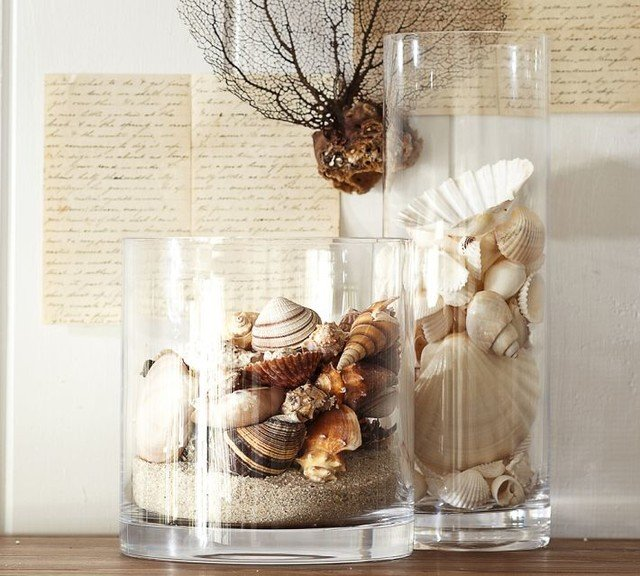 Closeup of two glass vases filled with sand and seashells