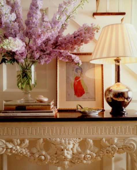 Closeup of entry table with a gold lamp and large vase of tall purple flowers