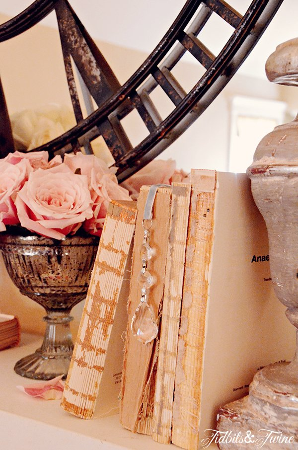 Fireplace mantel decorated with vintage books and crystal