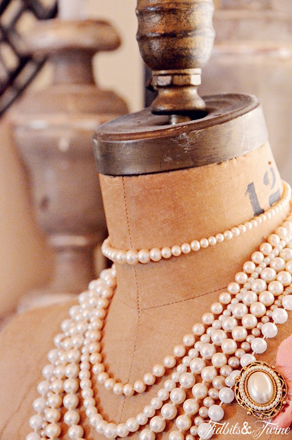 Closeup of vintage dress form with pearl necklaces and a pearl broach