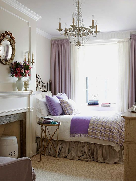 French style bedroom with white fireplace purple curtains and purple accents on the bed