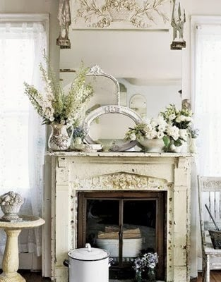 Antique white fireplace with a collection of mirrors and flowers on the mantel