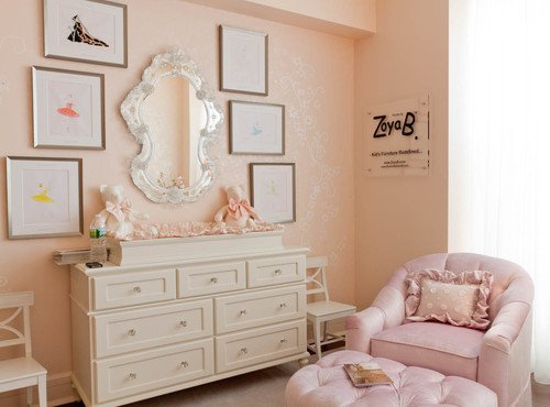 Girls room with pink walls and pink swivel chair and gallery wall over dresser