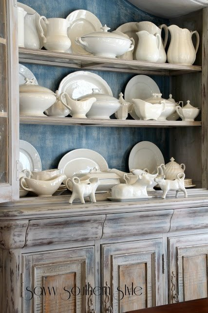 White ironstone collection in a dining hutch with blue inside