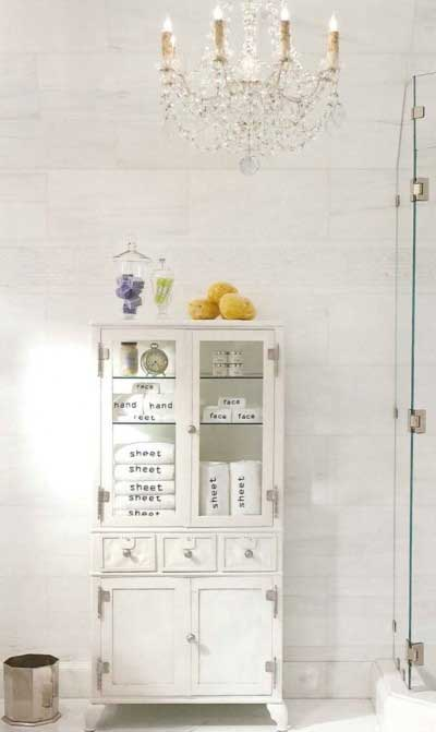 {A vintage medical cabinet has both form and function when used in the bath to hold toiletries. Image via The Perfect Bath.}