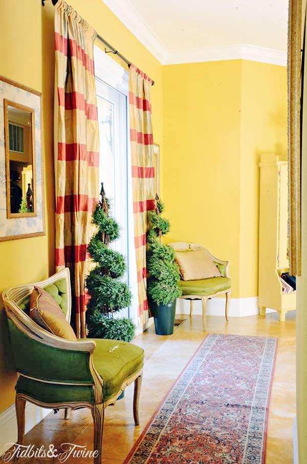Yellow hallway in european home with green accent chairs and plaid curtains