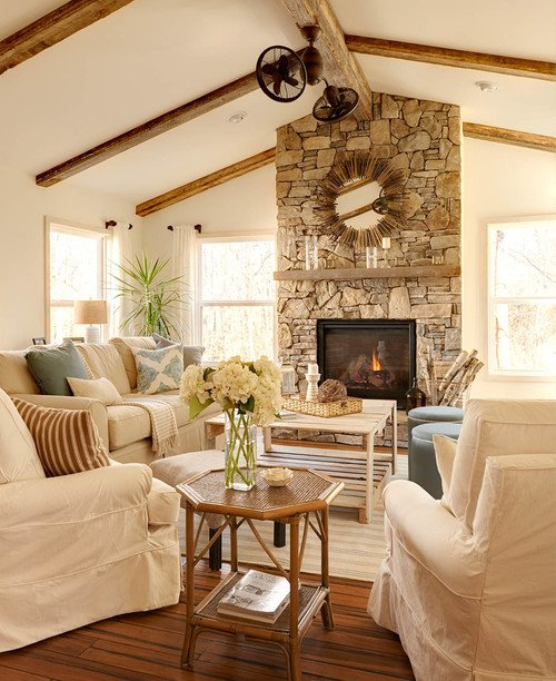 A beach style sunroom with white slipcovered furniture and light blue accepts and stone fireplace