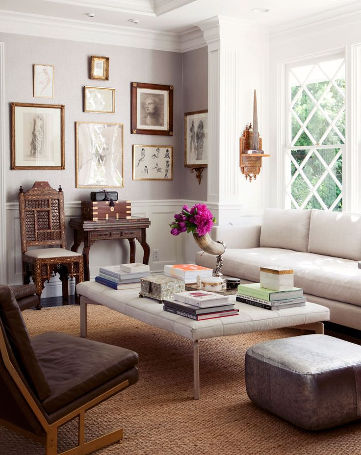 Eclectic living room with gallery wall and tufted ottoman holding books