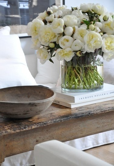 Huge vase of white flowers on top of a rustic wood coffee table