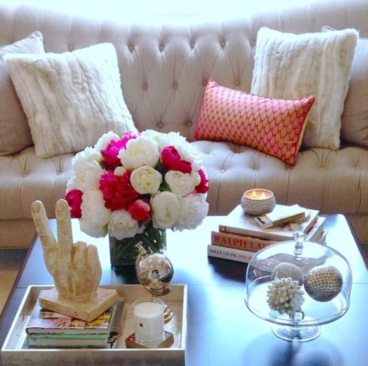 Coffee table with items in each of the four corner pink and white flowers and tufted sofa