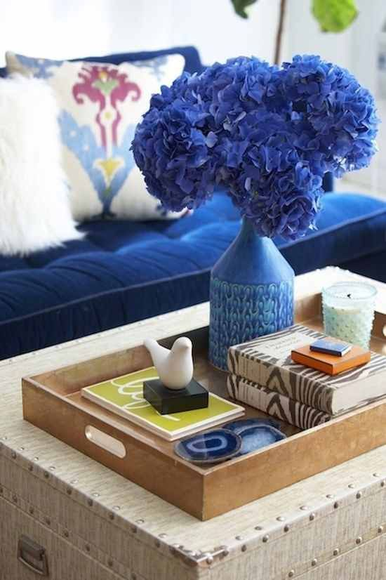 Trunk coffee table with brown tray on top and blue hydrangeas in a blue vase