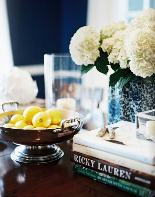 Closeup of coffee table with a bowl of lemons stack of books and hydrangeas