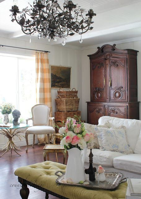 A French style living room with white slipcovered sofa and light green tufted ottoman and baskets stacked in corner