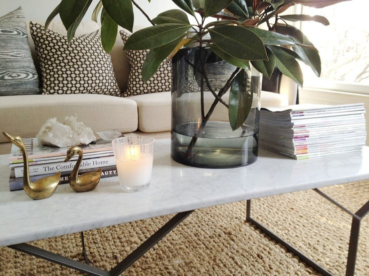Marble coffee table with vase of magnolia leaves on top and stacks of magazines