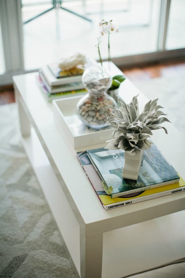 Closeup of white coffee table with an air plant and small orchid on top