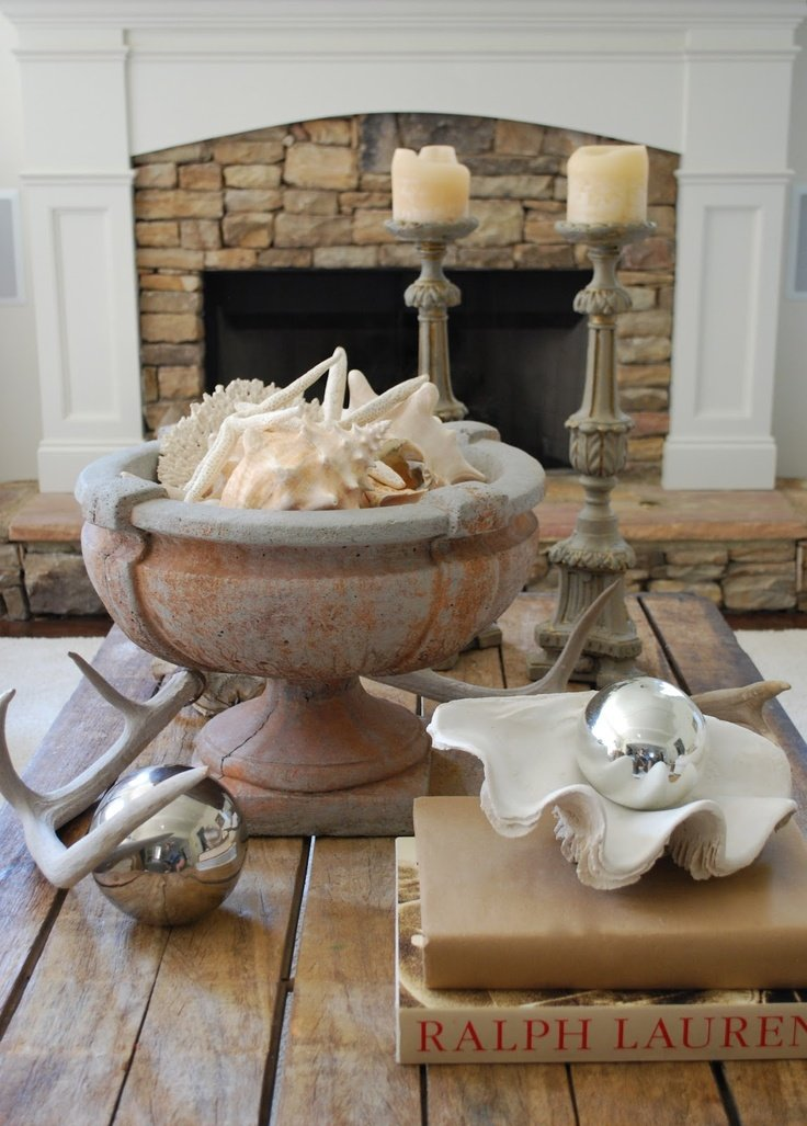 Industrial coffee table with urn holding seashell collection and two large candlesticks