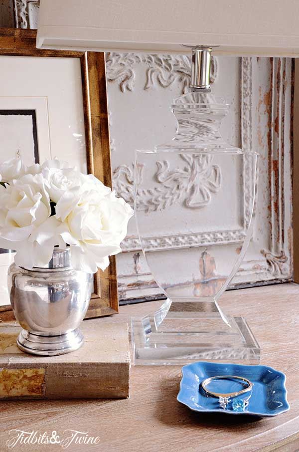 French nightstand with french-wired crystal lamp and silver vase of roses