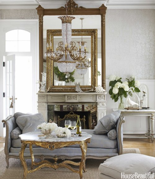 elegant french living room with two gold mirrors above fireplace and blue settee