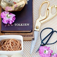 tray holding gold scissors and antique scissors with a gold vase holding pencils some purple flowers and white container of rubber bands