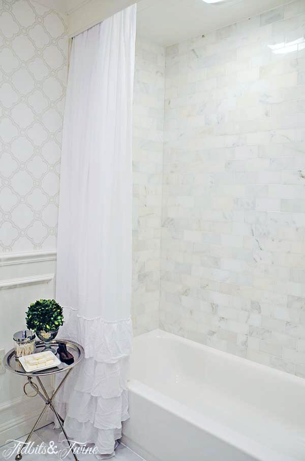 tub shower combo with marble subway tile and white ruffle shower curtain