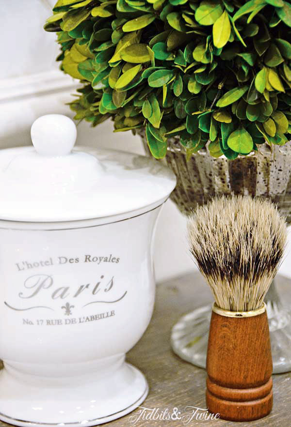 French bathroom container holding q-tips and mercury glass compote with preserved boxwood bathroom decor