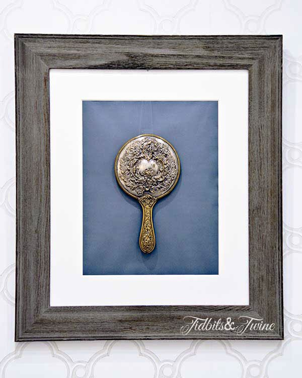 vintage silver hand mirror framed and hanging on bathroom wall